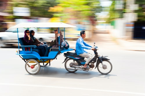 Cambodia Travel Photography Motion Blurred Photo of Tourists in a Tuktuk Speeding Along the Streets of Siem Reap Cambodia Southeast Asia