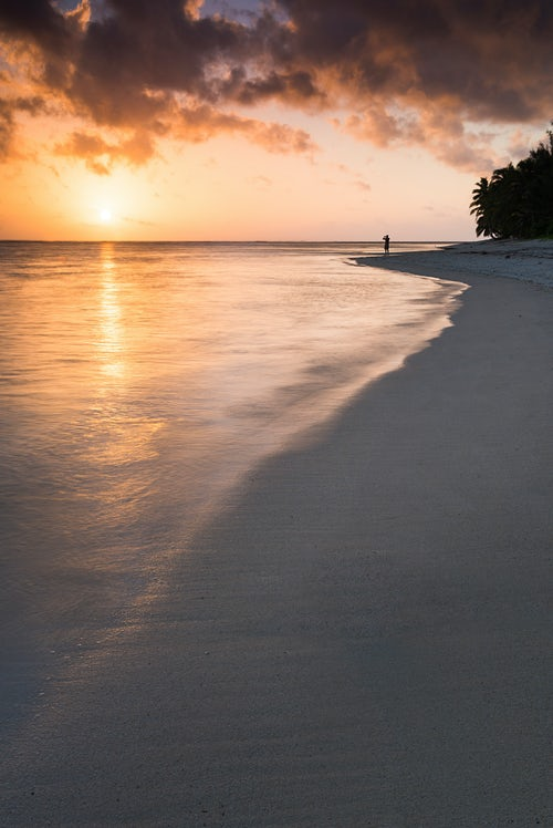 Cook Islands Landscape Travel Photography Person watching the tropical sunrise with dramatic orange clouds over the Pacific Ocean Rarotonga Island Cook Islands background with copy space