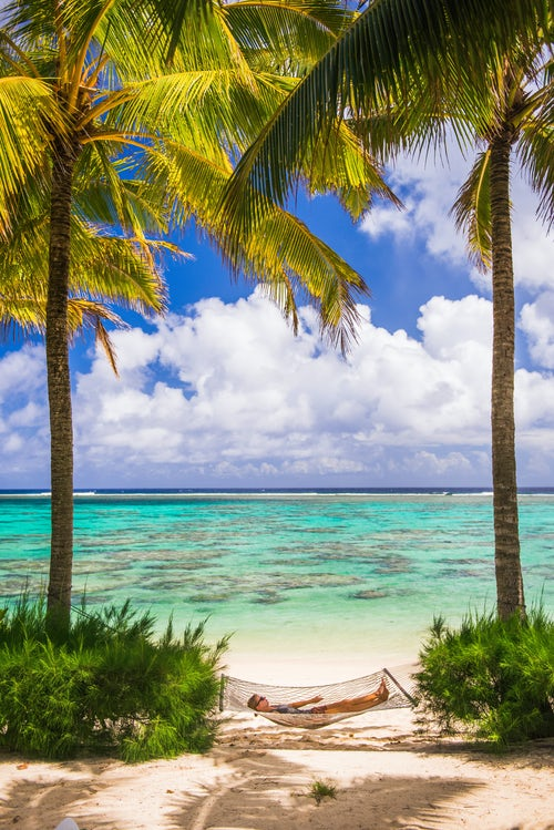Cook Islands Landscape Travel Photography Woman relaxing in a hammock under palm trees on the white sandy beach on the tropical island of Rarotonga Cook Islands South Pacific Ocean