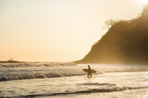 Costa Rica Travel Landscape Photography Surfers surfing on a beach at sunset Nosara Guanacaste Province Pacific Coast Costa Rica
