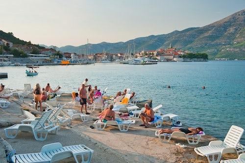Croatia Travel Photography Tourists sunbathing in Korcula Town Korcula Island Dalmatia Dalmacija Croatia