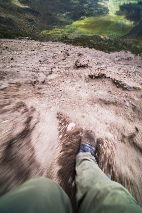 Ecuador Travel Photography Ruminahui Volcano climber sliding down volcanic sand slope Cotopaxi National Park Ecuador South America