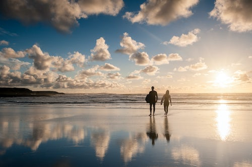 England Travel Photography Couple surfing at Constantine Bay at sunset Cornwall England United Kingdom Europe