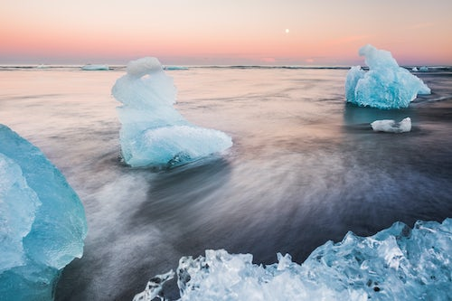 Iceland Landscape Photography Icebergs at sunset on Jokulsarlon Beach a black volcaic sand beach in South East Iceland