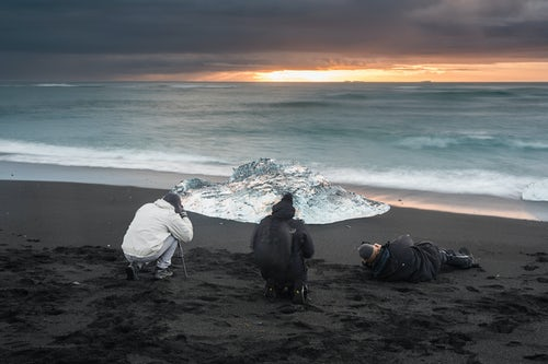 Iceland Landscape Photography Tourists taking a photo of icebergs at sunrise on Jokulsarlon Beach a black volcanic sand beach in South East Iceland Europe