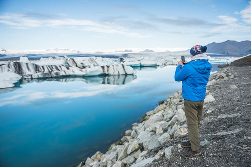 Iceland Travel Photography Tourist at Jokulsarlon Glacier Lagoon a glacial lake filled with icebergs in South East Iceland Europe