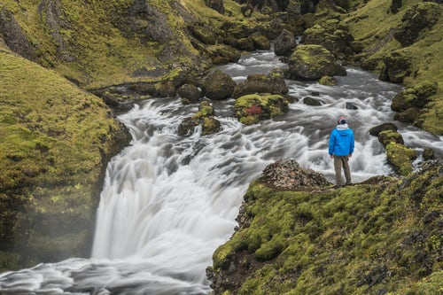Iceland Travel Photography Tourist at a waterfall on the hiking trail above Skogafoss Waterfall Skogar South Region Sudurland Iceland