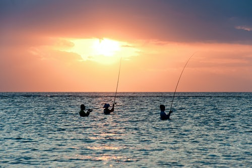 Indonesia Documentary Travel Photography Fisherman fishing at Sunset in teh ocean on Sengiggi Beach silhouetted against the sun Lombok Indonesia Asia background with copy space