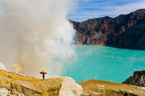 Indonesia Documentary Travel Photography Sulphur worker appearing out of toxic fumes at Kawah Ijen East Java Indonesia Asia Asia