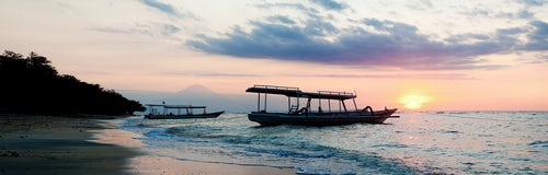 Indonesia Travel Photography Panoramic Photo of a Traditional Indonesian Boat Silhouetted Against the Sunset over Bali from Gili Trawangan Gili Isles Indonesia Asia