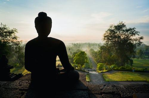 Indonesia Travel Photography Stone Buddha silhouetted at sunrise at Borobudur Temple UNESCO World Heritage Site Yogyakarta Java Indonesia Asia Asia