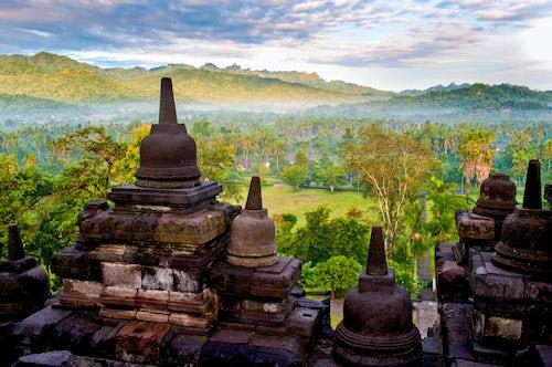 Indonesia Travel Photography Stone Stupas and Early Morning Mist on the Kedu Plain During Sunrise at Borobudur Temple Yogyakarta Java Indonesia Asia