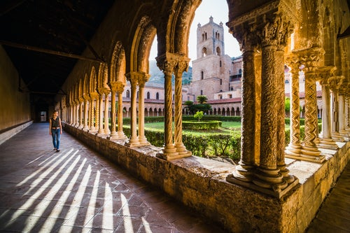 Italy Sicily Travel Photography Tourist at Monreale Cathedral Duomo di Monreale walking through columns in the courtyard gardens at sunset Monreale near Palermo Sicily Italy Europe