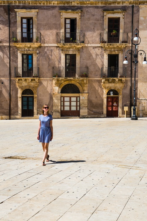 Italy Sicily Travel Photography Woman on holiday in Piazza Duomo in Ortigia Syracuse Siracusa UNESCO World Heritage Site Sicily Italy Europe