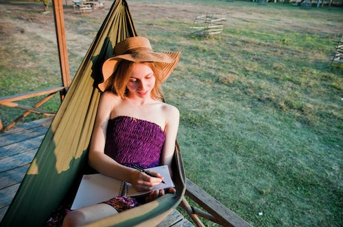 Laos Travel Photography Tourist Writing her Diary in a Hammock at Bamboo Accommodation in Vang Vieng Laos Southeast Asia