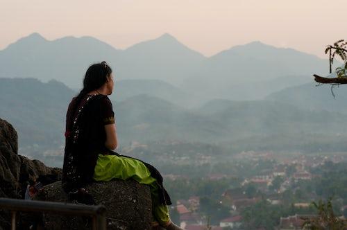 Laos Travel Photography Woman Watching the Sun Set from Wat Phousi Luang Prabang Loas Southeast Asia