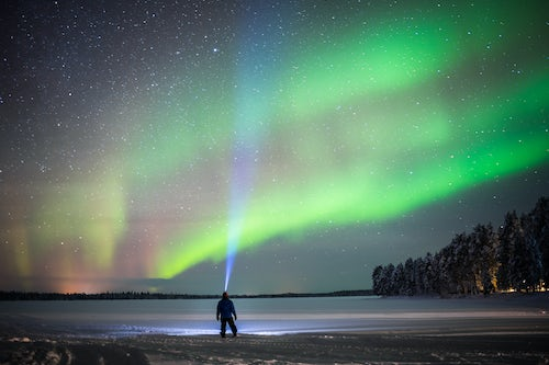 Lapland Finland Adventure Travel Photography Person under Northern Lights aurora borealis display of amazing bright colourful green and purple and stars in sky in Lapland inside Arctic Circle in Finland