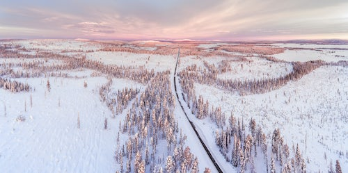 Lapland Finland Drone Landscape Photography Icy snow covered winter road in the Arctic Circle at sunset in Lapland Finland