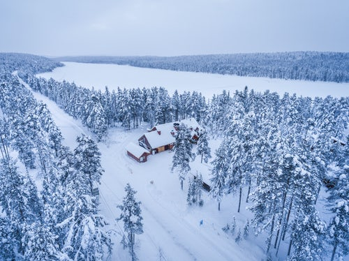 Lapland Finland Travel Photography Aerial drone photos of cabins huts and accommodation in the forest with snow covered winter landscape and trees in woods Torassieppi Arctic circle in Finnish Lapland Finland