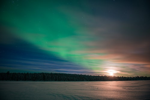 Northern Lights Landscape Photography Northern Lights aurora borealis and moon seen over a snow covered lake in winter in Finnish Lapland inside Arctic Circle in Finland