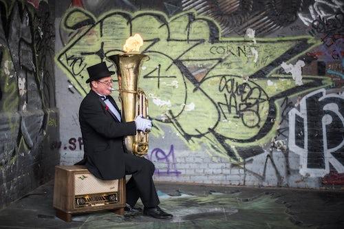 London Street Photography Street performer busking with a fire filled tuba on Clink Street near Borough Market Southwark London England