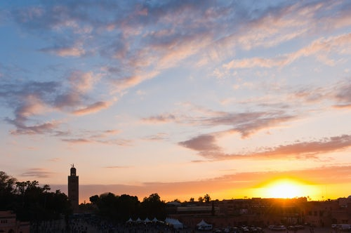 Morocco Travel Photography Koutoubia Mosque minaret silhouetted at sunset taken from Place Djemaa El Fna Square Marrakech Marrakesh Morocco North Africa Africa background with copy space