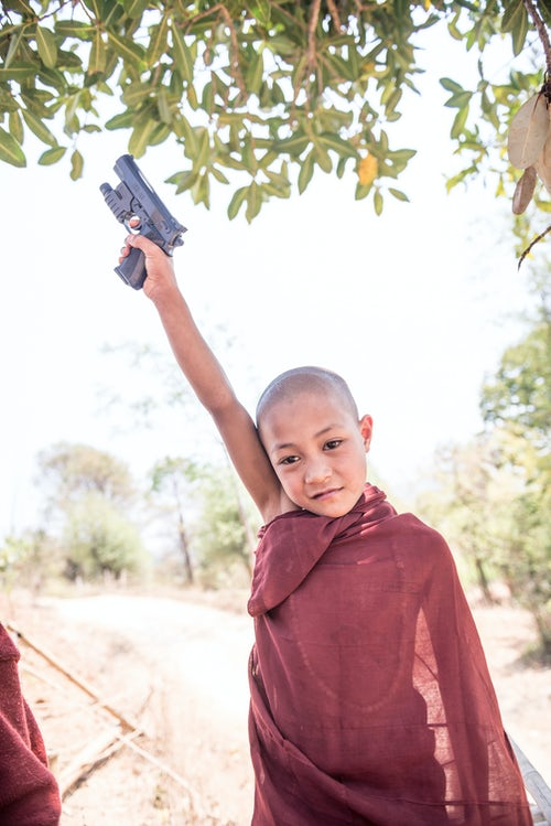 Myanmar Burma Portrait Travel Photography Documentary Portraiture Novice Monk with a toy gun at a Buddhist Monastery between Inle Lake and Kalaw a popular 2 day trek in Shan State Myanmar Burma