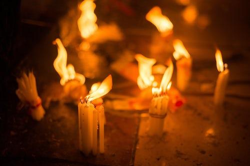 Myanmar Burma Travel Photography Candles burning at Golden Rock Kyaiktiyo Pagoda at night Mon State Myanmar Burma