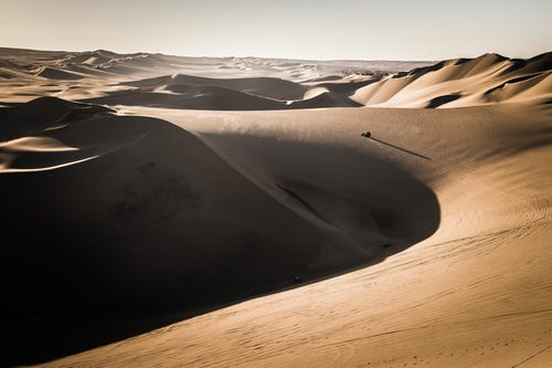 Peru Travel Photography Dune buggying in sand dunes at sunset in the desert at Huacachina Ica Region Peru South America