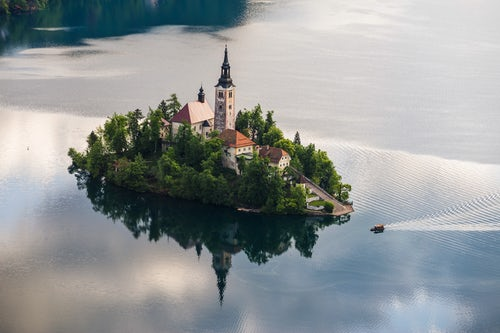 Slovenia Landscape Photography Lake Bled rowing boat at sunrise arriving at the Church of the Assumption of St Mary on Lake Bled Island Gorenjska Slovenia Europe