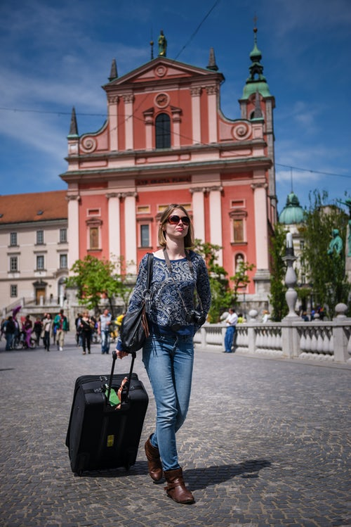 Slovenia Travel Photography Tourist arriving with suitcase walking past the Franciscan Church of the Annunciation in Presernov Trg Preseren Square Ljubljana Slovenia Europe