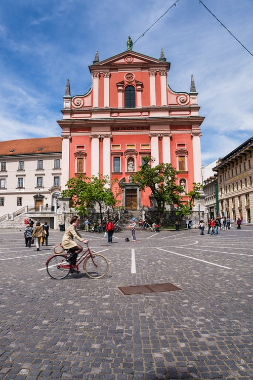 Slovenia Travel Photography Tourist cycling past the Franciscan Church of the Annunciation in Presernov Trg Preseren Square Ljubljana Slovenia Europe
