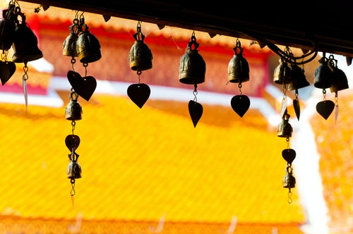 Thailand Travel Photography Close up of prayer bells silhouetted against the colourful roof at Wat Doi Suthep Chiang Mai Thailand Southeast Asia