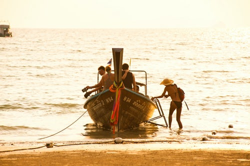 Thailand Travel Photography Tourists in a Traditional Thai Boat at Sunrise on East Railay Beach Rai Leh South Thailand Southeast Asia
