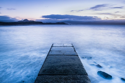 Wales Landscape Photography Long exposure calm tranquil scene of waves and the ocean with a pier at Criccieth Beach at sunrise North Wales United Kingdom