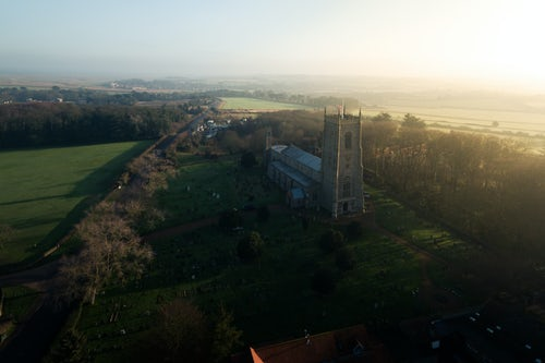 Drone Photography by UK London Freelance Drone Photographer Aerial drone photo of Blakeney church in North Norfolk England UK in beautiful sunlight in the typical English countryside with green fields and farmland