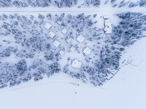 Drone Photography by UK London Freelance Drone Photographer Aerial drone photos of cabins huts and accommodation in the forest with snow covered winter landscape and trees in woods