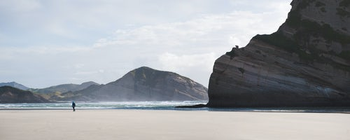 Landscape Photography by Professional Freelance UK Landscape Photographer Panoramic Photo of a Backpacker Walking Along Deserted Windy Wharariki Beach Golden Bay South Island New Zealand