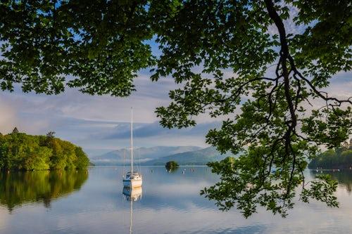 Landscape Photography by Professional Freelance UK Landscape Photographer Sailing boat floating on Lake Windermere at sunrise Lake District National Park Landscape Cumbria England UK Europe